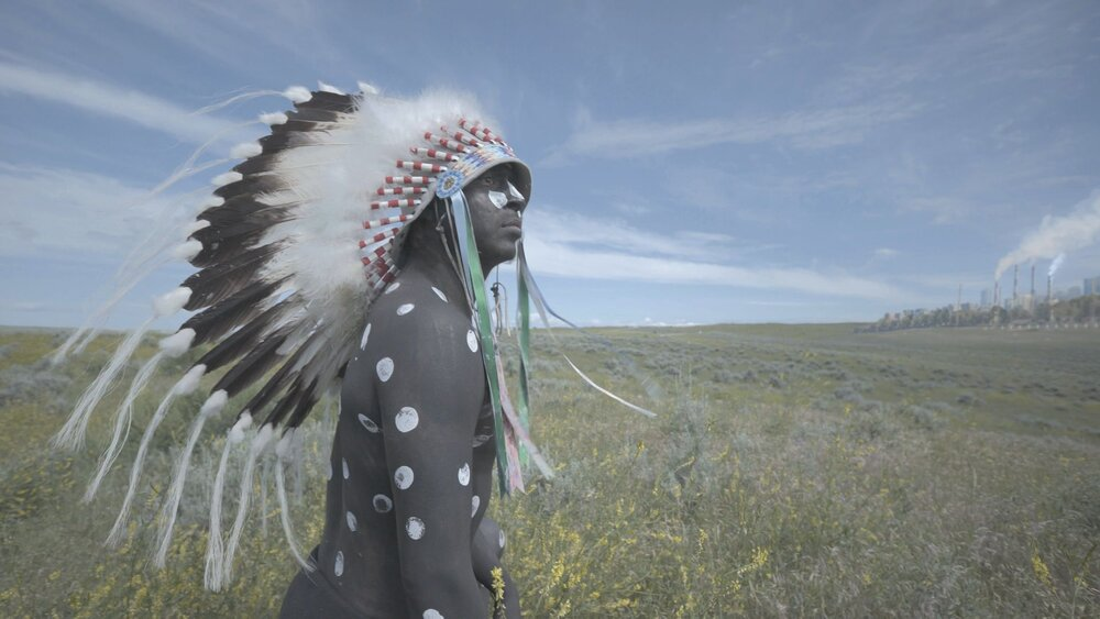 A video still of an indigenous person in body paint and a headdress.